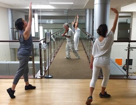 Violinist Anthony Hyatt leads dancers through MedStar Georgetown University Hospital in Washington.