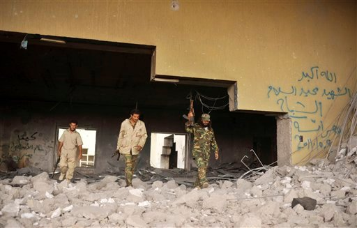 Libyan rebels walk out from the destroyed palace of their country's ousted leader Muammar Qaddafi, in Sirte, Libya, Monday, Oct. 10, 2011.