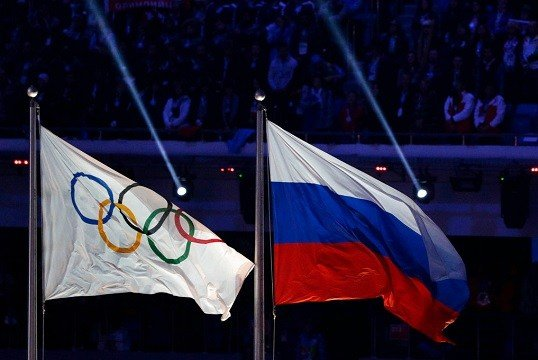 Russian national flag, right, flies next to the Olympic flag during the closing ceremony of the 2014 Winter Olympics in Sochi, Russia.