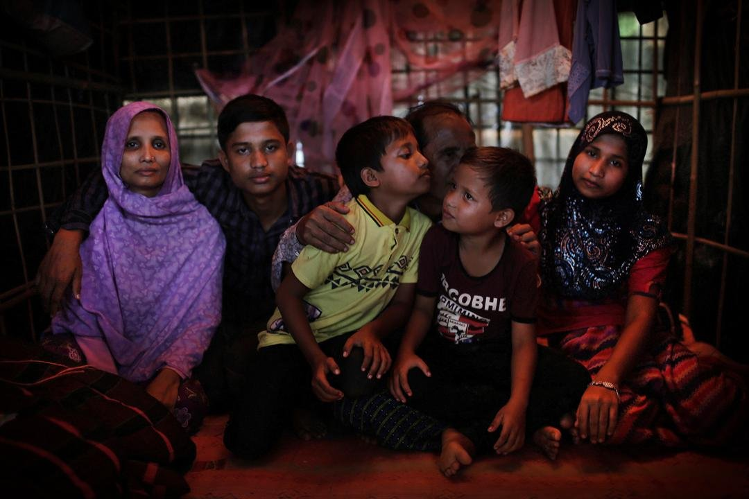 In this Nov. 25, 2017, photo, Bodru Duza, 52, third from right, kisses his sons as he sits for a portrait with members of his family in a tent in Kutupalong refugee camp in Bangladesh. (AP Photo/Wong Maye-E)