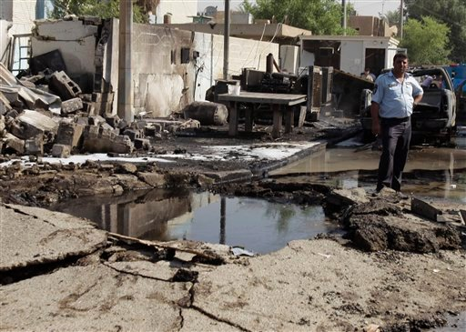 An Iraqi policeman inspects a crater caused by a car bomb attack in front of a police station in Baghdad, Iraq, Wednesday, Oct. 12, 2011. (AP Photo/Karim Kadim)