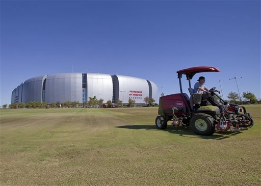 Groundskeepers mow the lawns outside University of Phoenix Stadium Oct. 11, 2011, in Glendale, Ariz. NFL owners have awarded the 2015 Super Bowl to the Phoenix area on Tuesday.(AP Photo/Matt York)