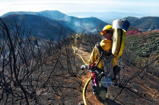 Santa Barbara County Firefighters haul dozens of pounds of hose and equipment down steep terrain.