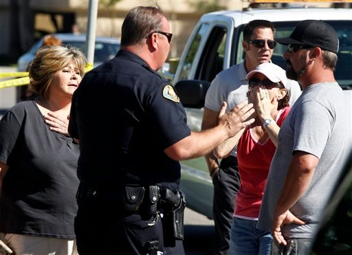 A police officer talks to onlookers near the site where six people were killed and three were wounded in a shooting at a hair salon in Seal Beach, Calif., Wednesday, Oct. 12, 2011.