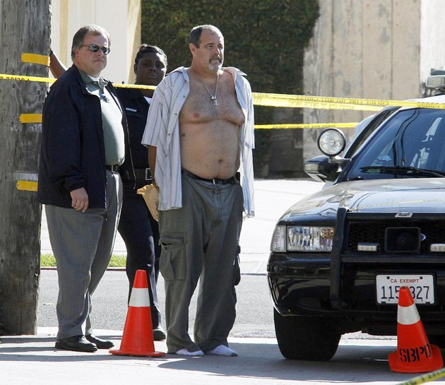 Police officers stand with a man who was being held in a patrol car at the scene of the arrest of a suspect near the Salon Meritage in Seal Beach, Calif., where a shooting left six people dead and three critically injured Wednesday, Oct. 12, 2011.