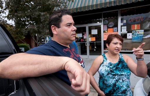 Jose Contreras and his wife Nelva discuss the reasons for closing their Hispanic store and restaurant (rear) in Albertville, Ala., Wednesday, Oct. 12, 2011.