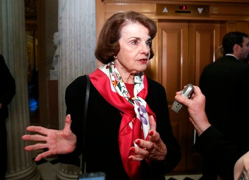 FILE--In this Dec. 19, 2017, file photo, Sen. Dianne Feinstein, D-Calif., speaks with a reporter on Capitol Hill in Washington. Feinstein says she won't vote for a stopgap spending measure to keep the U.S. government open if it doesn't include protections