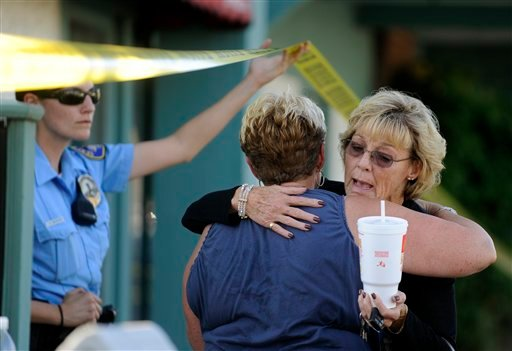 Women hug near the Salon Meritage in Seal Beach, Calif. where nine people were shot, Wednesday, Oct. 12, 2011. (AP Photo/Chris Carlson)