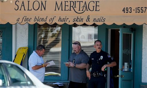 Investigators stand near the site where six people were killed and three were wounded in a shooting at a hair salon in Seal Beach, Calif., Wednesday, Oct. 12, 2011. (AP Photo/Chris Carlson)