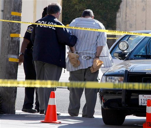 Police officers stand with a man being held in a patrol car at the scene of the arrest of a suspect near the Salon Meritage in Seal Beach, Calif., where a shooting left eight people dead and one critically injured Oct. 12, 2011. (AP Photo/Reed Saxon)