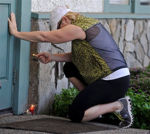 Elaine Metz, of Seal Beach. Calif., lights a candle in front of the site where eight people were killed and one was wounded Wednesday in a shooting at Salon Meritage in Seal Beach, Calif., Thursday, Oct. 13, 2011. (AP Photo/Chris Carlson)