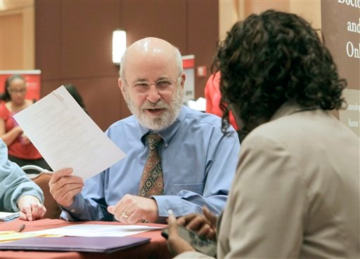 In this Sept. 13, 2011 photo, Pierre Daunic, Ph.D., a senior writer with Fast Forward Career services works with applicants at a job fair at the Crowne Plaza Hotel in Orlando, Fla. (AP Photo/John Raoux)