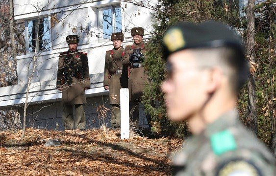 North Korean soldiers look at the South side as a South Korean stands guard near the spot where a North Korean soldier crossed the border.