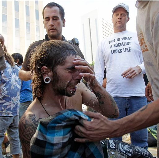 A demomstrator tries to wash pepper spray from his eyes after a clash with the San Diego Police at the Civic Center Plaza Friday, Oct. 14, 2011 in San Diego.