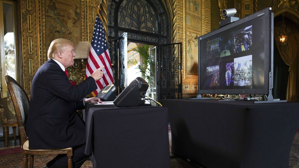 President Donald Trump points to the video screen during a Christmas Eve video teleconference with members of the mIlitary at his Mar-a-Lago estate in Palm Beach, Fla., Sunday, Dec. 24, 2017. (AP Photo/Carolyn Kaster)
