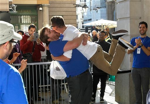 A customer jumps into the arms of an Apple employee outside the Apple Store in Covent Garden, to celebrate his purchase of the new iPhone 4S, which went on sale in London, Friday, Oct. 14, 2011. (AP Photo/Kirsty Wigglesworth)