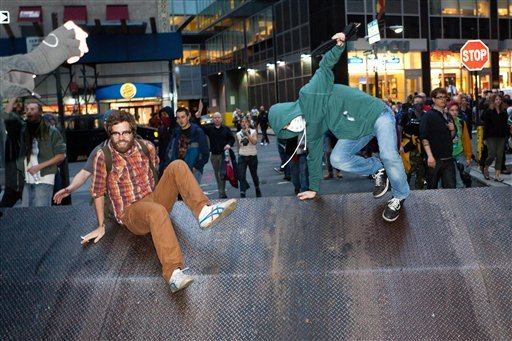 Occupy Wall Street protestors leap over a vehicle barricade as hundreds march towards Wall Street after being heartened by a postponement of a scheduled cleanup Oct. 14, 2011, in New York. (AP Photo/John Minchillo)