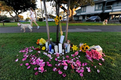 A woman runs with her dog past a makeshift memorial near the site where eight people were killed and one was wounded in a shooting at Salon Meritage on Thursday, Oct. 13, 2011, in Seal Beach, Calif. (AP Photo/Chris Carlson)