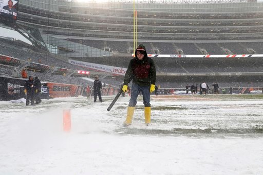 A worker clears snow from Soldier Field before an NFL football game between the Chicago Bears and Cleveland Browns in Chicago, Sunday, Dec. 24, 2017. (AP Photo/Nam Y. Huh)