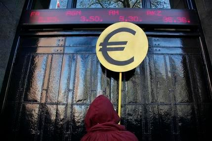A hooded protestor holding a Euro sign walks up to the gate of the NYSE Euronext stock exchange in Amsterdam, Netherlands, Saturday Oct. 15, 2011. (AP Photo/Peter Dejong)