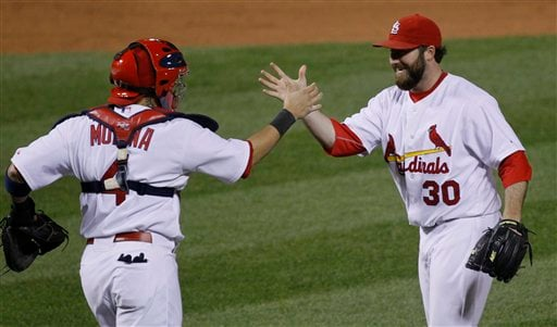St. Louis Cardinals' Jason Motte (30) celebrates with catcher Yadier Molina after Game 5 of baseball's National League championship series against the Milwaukee Brewers Friday, Oct. 14, 2011, in St. Louis. (AP Photo/Charles Rex Arbogast)