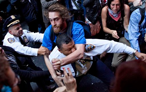 A man affiliated with the Occupy Wall Street protests tackles a police officer during a march towards Wall Street in New York, on Friday, Oct. 14, 2011. (AP Photo/Andrew Burton)