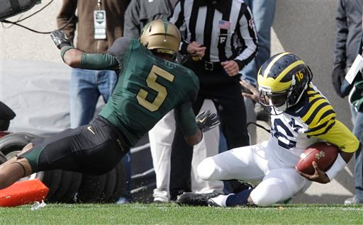 Michigan quarterback Denard Robinson, right, falls into the end zone to score a touchdown as Michigan State cornerback Johnny Adams (5) defends during the first quarter of an NCAA college football game Oct. 15, 2011. (AP Photo/Carlos Osorio)