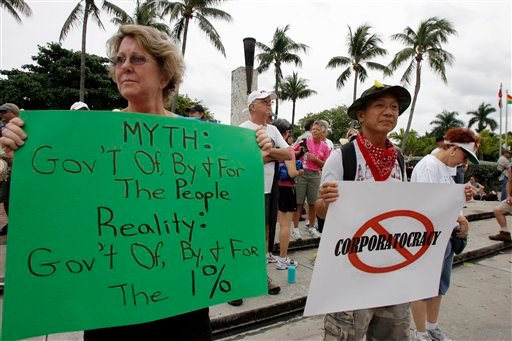 Marilyn Bernardy left, and Manny Paz right, join hundreds of demonstrators protesting for Occupy Florida at the Torch of Friendship on Saturday Oct. 15, 2011 in Miami. (AP)