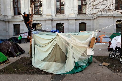 Nicholas Molinuevo, left in tree, works on his tent in the park around City Hall Sunday, Oct. 16, 2011 in Philadelphia. (AP)