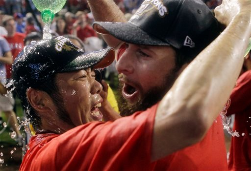 Texas Rangers' Koji Uehara of Japan and Scott Feldman celebrate winning Game 6 of baseball's American League championship series against the Detroit Tigers 15-5, Saturday, Oct. 15, 2011, in Arlington, Texas. (AP)