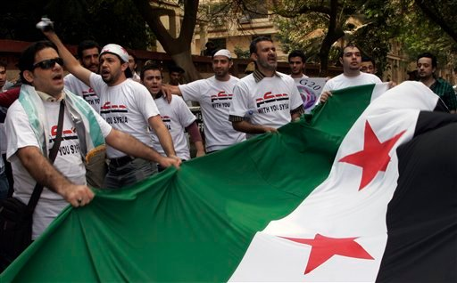 Men hold a Syrian national flag during a demonstration against President Bashar Assad in front of the Syrian embassy in Cairo, Egypt, Saturday, Oct. 15, 2011. (AP Photo/Mohammed Abu Zaid)