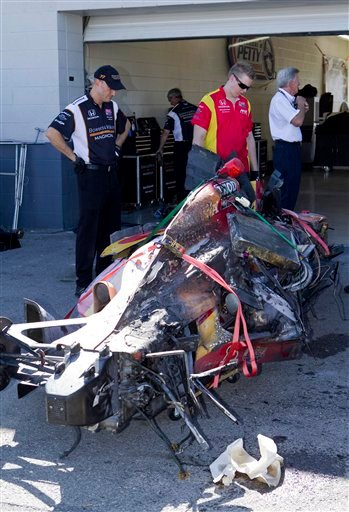 Crew members stare at a wrecked car after a crash that involved 15 cars early in the IndyCar Series' Las Vegas 300 Indy auto race Sunday, Oct. 16, 2011, in Las Vegas. (AP Photo/Eric Jamison)