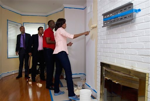 First lady Michelle Obama, right, paints in the home of Army Sgt. Johnny Agbi, second from left, during a Joining Forcers initiative event, Monday, Oct. 17, 2011, in Washington.