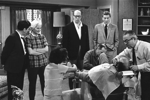 "FILE- In this April 11, 1963, file photo, standing from left, Morey Amsterdam, Rose Marie, and Richard Deacon, and Dick Van Dyke, right, gather around Carl Reiner, in barber chair during a rehearsal of an episode for the ""The Dick Van Dyke Show."""