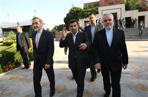 Iranian President Mahmoud Ahmadinejad, center, gestures to the photographer at Tehran's Mehrabad airport, Iran, Monday, Sept. 19, 2011, before his departure for New York to attend the UN General Assembly.
