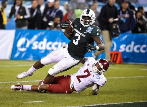 Michigan State running back LJ Scott (3) scores over Washington State defensive back Robert Taylor (2) on a 28-yard run during second half of the Holiday Bowl NCAA college football game Thursday, Dec. 28, 2017, in San Diego. (AP Photo/Denis Poroy)