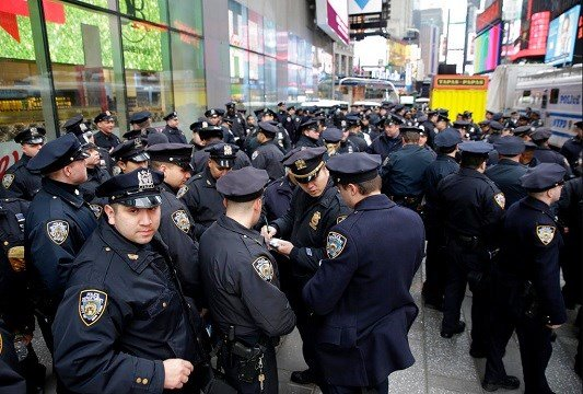 Police officers gather at the southern end of Times Square to receive their assignments for New Year's Eve in New York.