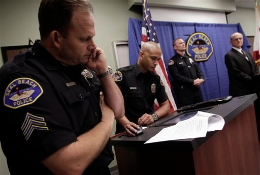 Seal Beach police Sgt. Steve Bowles, from left, crime analyst Kevin Edwards, Capt. Tim Olson and Police Chief Robert Luman listen to recordings of 911 calls reporting last week's shootings at Salon Meritage during a news conference in Seal Beach, CA.