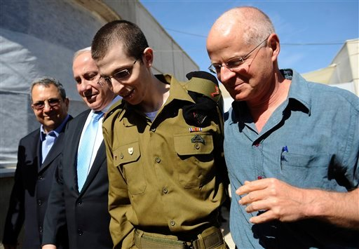 In this photo released by the Israeli Government Press Office, released Israeli soldier Gilad Schalit is escorted by his father, Noam Schalit, right, Prime Minister Benjamin Netanyahu and Defense Minster Ehud Barak as he arrives at Tel Nof Air base.