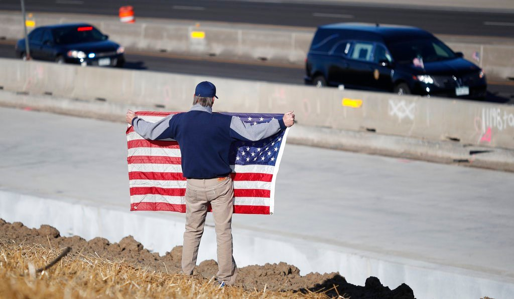 David Morgan of Highlands Ranch, Colo., holds an American flag as a procession of law enforcement vehicles accompany a hearse carrying the body of a sheriff's deputy shot and killed in Highlands Ranch, Colo. (AP Photo/David Zalubowski)