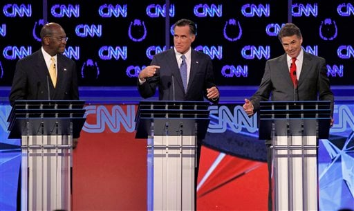 Republican presidential candidates businessman Herman Cain, left, watches as former Massachusetts Gov. Mitt Romney, center, and Texas Gov. Rick Perry speak during a Republican presidential debate Oct. 18, 2011, in Las Vegas. (AP Photo/Chris Carlson)