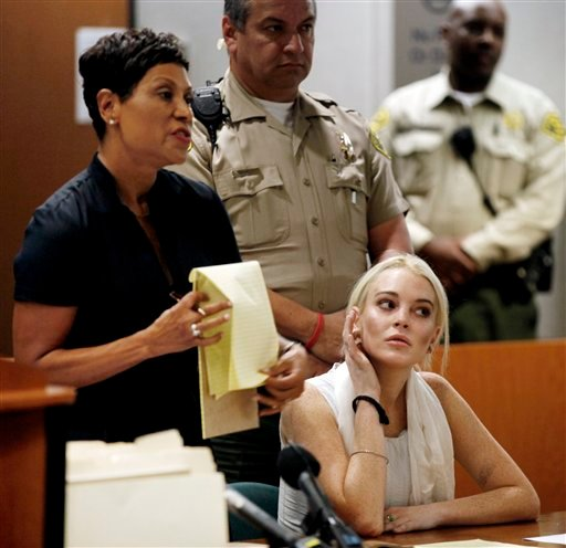 Lindsay Lohan, right, alongside her attorney Shawn Chapman Holley, is shown before being taken into custody by Los Angeles Country sheriffs deputies after a judge found her in violation of probation Wednesday, Oct. 19, 2011, in Los Angeles.