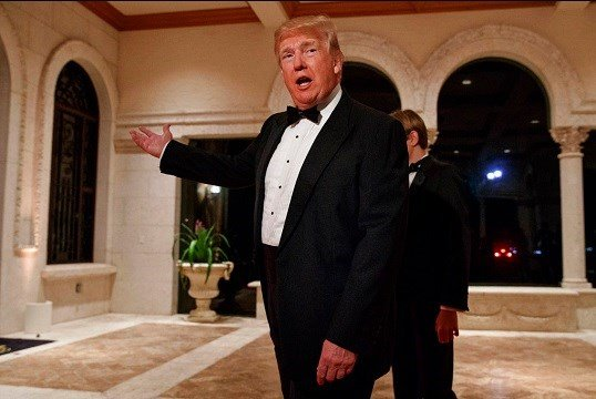 President Donald Trump speaks with reporters as he arrives for a New Year's Eve gala at his Mar-a-Lago resort, in Palm Beach, Fla.