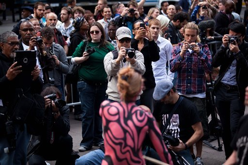 In this photo taken Tuesday, Oct. 18, 2011, spectators swarm the Occupy Wall Street protests with their cameras in Zuccotti Park in New York.