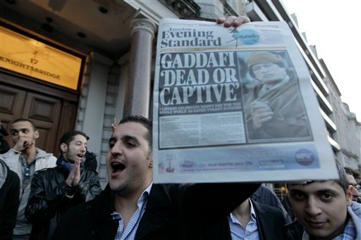 A Liyban holds up a newspaper and reacts to the death of Muammar Qaddafi outside the Libyan Embassy in London, Thursday, Oct. 20, 2011.