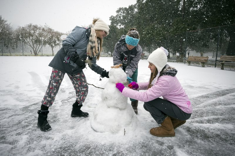 Children from the Hoffman and Lynns families build a snowman on the public basketball courts in Forsyth Park, Wednesday, Jan. 3, 2018, in Savannah, Ga. Georgia Gov.