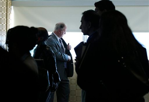 In this Oct. 17, 2011 photo, a man pauses by a window as job seekers wait to get information and drop off resumes during a job fair in Boston.