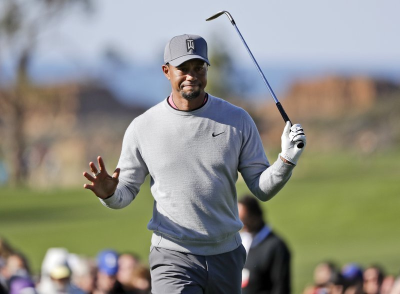 In this Jan. 27, 2017, file photo, Tiger Woods reacts after hitting out of the rough on the ninth hole of the North Course during the second round of the Farmers Insurance Open golf tournament at Torrey Pines Golf Course in San Diego.