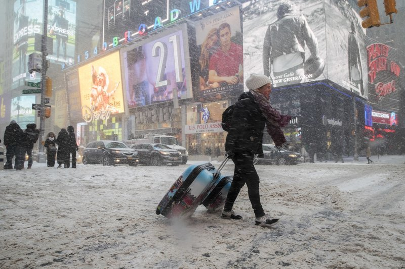 Rebecca Hollis of New Zealand drags her suitcases in a snowstorm through Times Square on her way to a hotel, Thursday, Jan. 4, 2018, in New York.