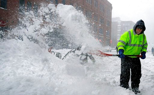 Workers clear snow from a sidewalk in the Seaport District of Boston, Thursday, Jan. 4, 2018. Forecasts for the Boston area call for about a foot of snow during the day and blizzard-like conditions.(AP Photo/Charles Krupa)